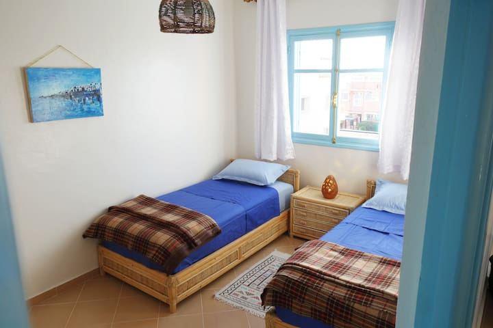 Bedroom with two beds of 90x190, high-quality mattresses, wardrobe and bedside table (all hand-fabricated in Essaouira)