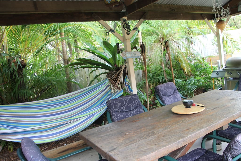 BBQ area in a cool rainforest setting with a large wooden table and comfortable chairs, gas BBQ and a cool hammock for a Nana nap.