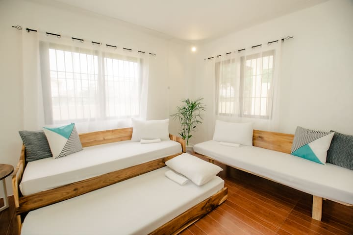 """Non-Airconditioned LIVING AREA  on the 1st floor will be used as bedroom for 3 guests. 8th-10th guests will occupy the sofa beds w/fresh beddings & blankets for comfort and may enjoy lounging while watching Netflix :)  20"""" Hurricane Fan is provided."""