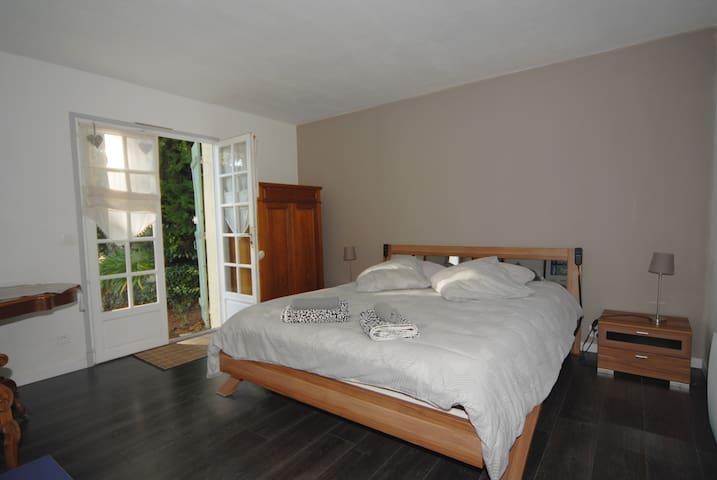 La chambre principale avec son lit double électrique ouvrant sur le jardin.