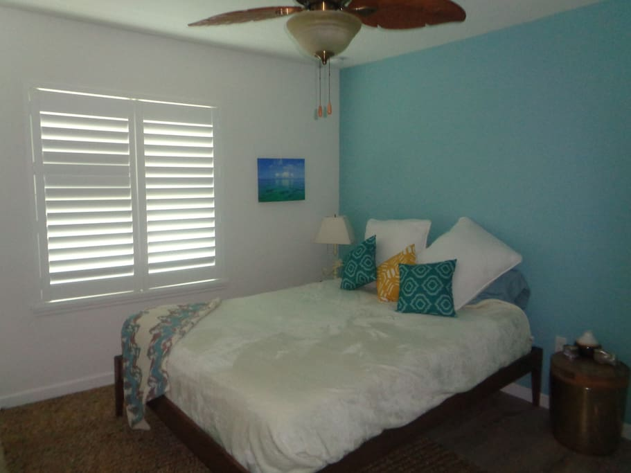 Tropical Inspired bedroom with Queen bed, new mattress and bedding. Closet space with hangers.