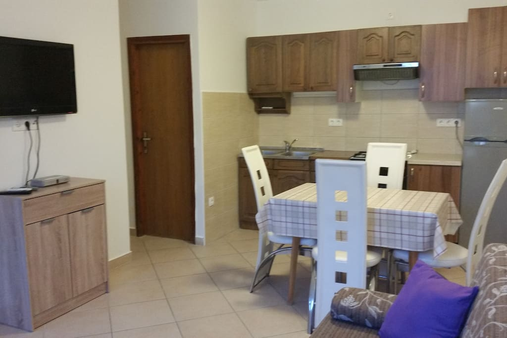 Fully equipped kitchen with living room. In kitchen is dining table. In living room is tv and a sofa for two.