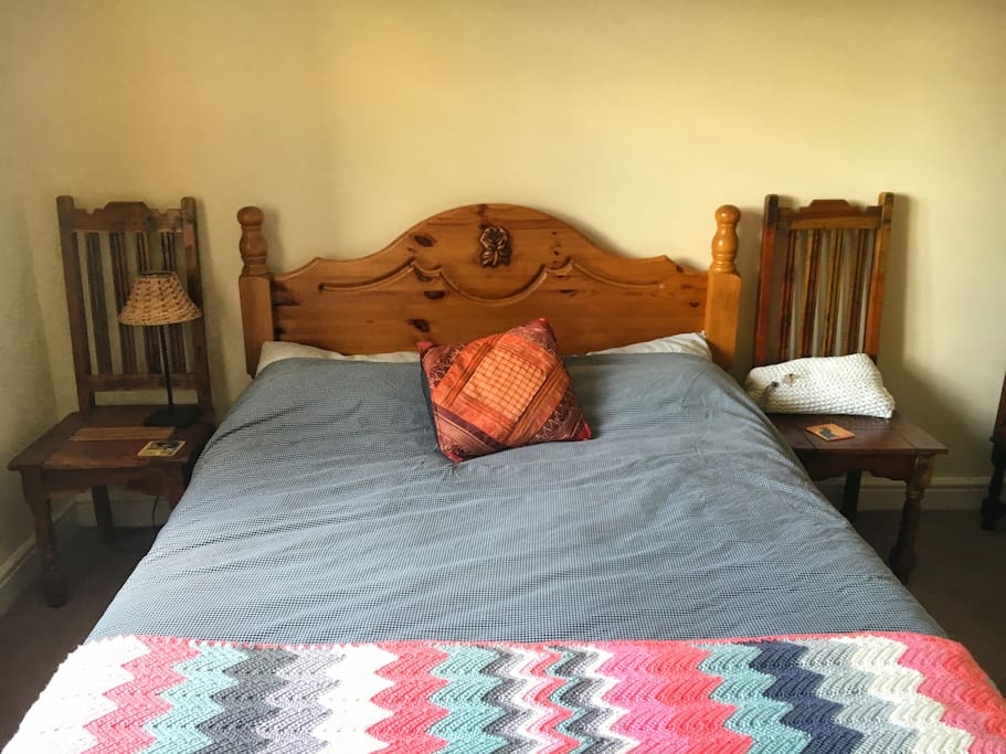 Double bed with the side tables made from antique chairs