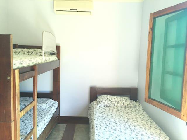 Quarto de hóspedes com ar-condicionado e ventilador de teto, bicama e beliche.
