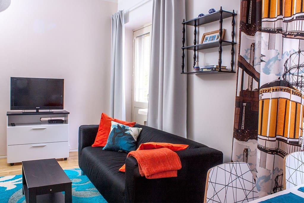Oleskelunurkassa sohva ja televisio. Oleskelutilan puolella ikkunoissa pimennysverhot. - Sofa corner with TV. Windows have black out curtains.