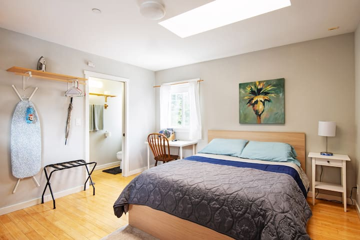 Studio with queen bed, desk, luggage rack, ironing board, iron, umbrella, hangers, hanging bar and door to bathroom
