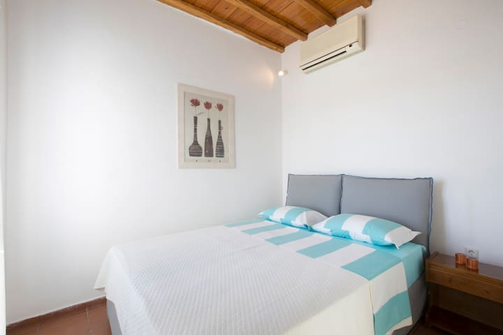 Double bedroom with ensuite bathroom, decorated in minimal Mykonos and Cycladic style.