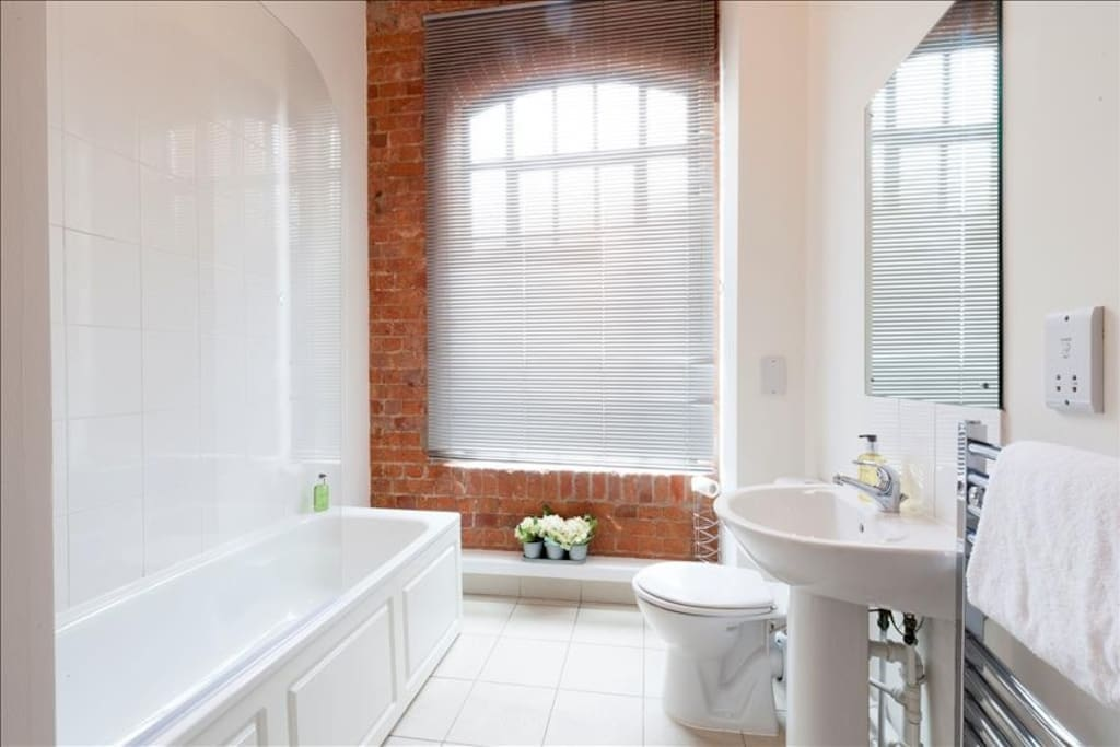 Large bright bathroom with shower over bath