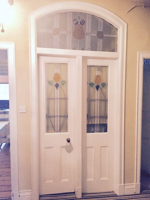 Stain glass door leading to spacious bathroom with separate bath and shower unit