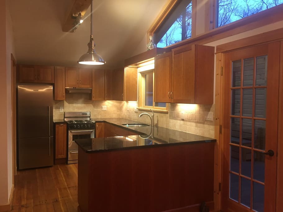 Brand new stainless steel refrigerator, gas stove and granite countertops framed in custom cabinets.