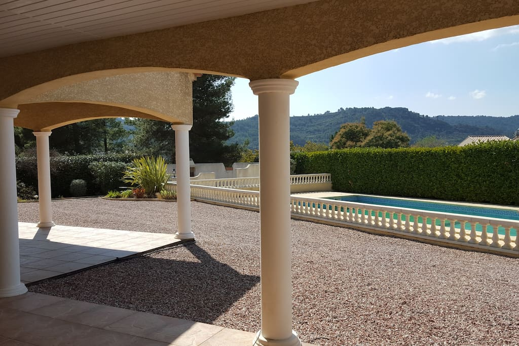 view from the terrace to the pool area and hills in Cessenon sur Orb