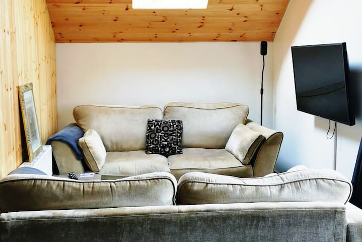 Cosy living area with smart TV. Perfect for relaxing after a forest walk.