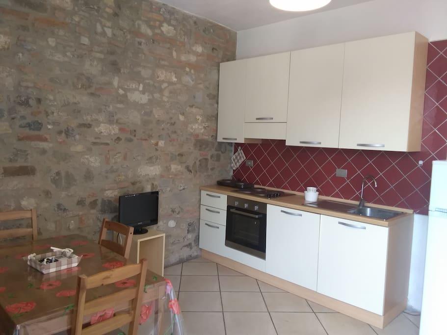 Cucina sala da pranzo con parete con sasso a vista