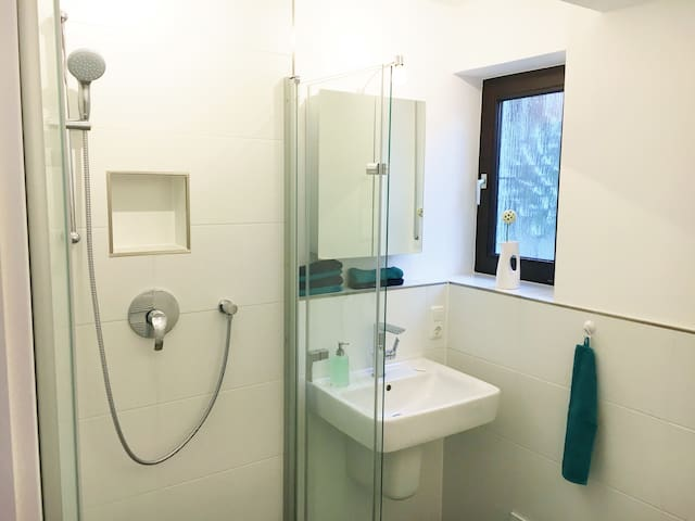 Barrierefreies Bad mit Fenster,  großzügiger Dusche, Fußbodenheizung und  zusätzlichem Handtuchheizkörper