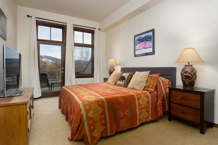Guest king bedroom, with TV and access to balcony.