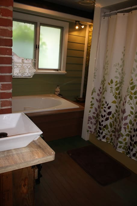 The private bathroom brings the outdoors inside with a woodland themed air-jet bath and whimsical, outdoor themed decor.
