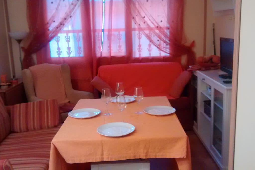 Salón comedor con mesa, sillas, sofá-cama, butaca, TV.