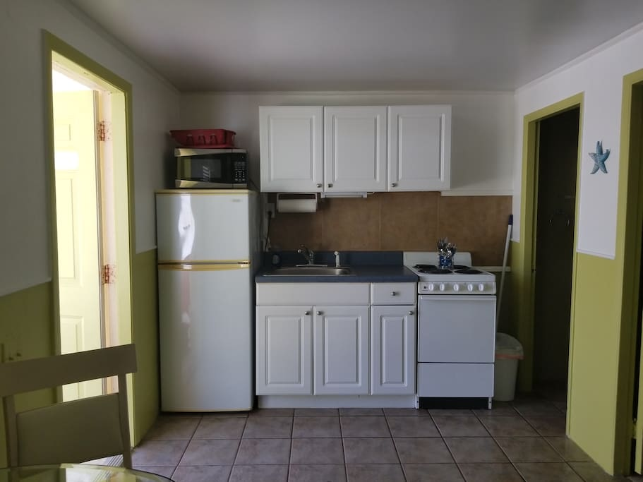 Fully equipped kitchen dishes utensils pots and pans microwave toaster coffee maker supplies coffee and creamer and sugar on nightly stays.