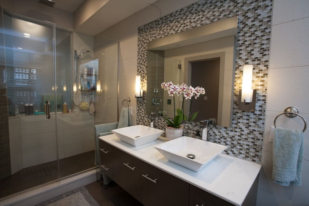 Master bathroom features double sink, walk-in rain shower for two, and custom tilework throughout.