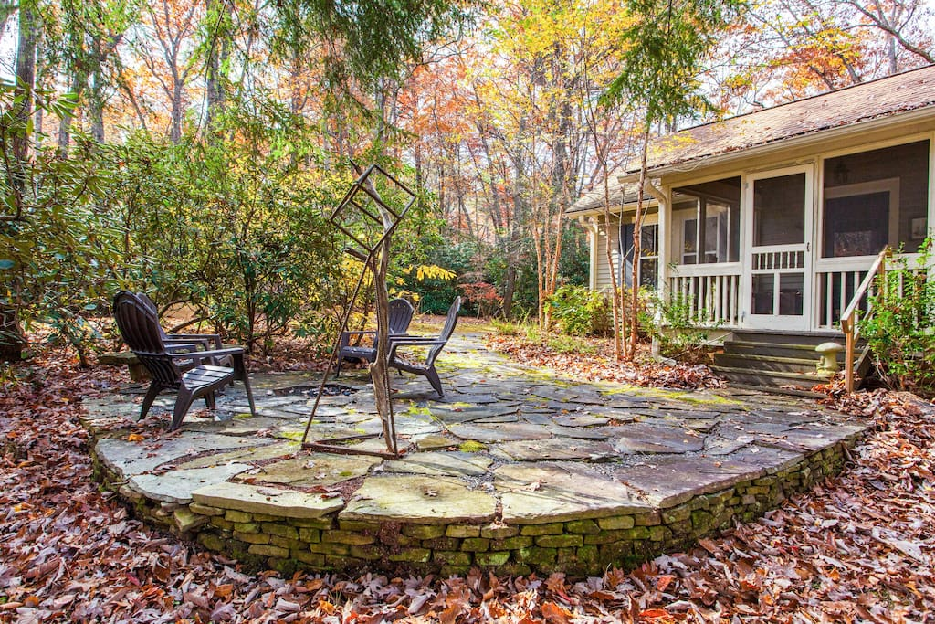 Woodsy patio with fire pit, seating for 4, and intriguing metal sculpture. Property professionally managed by TurnKey Vacation Rentals.