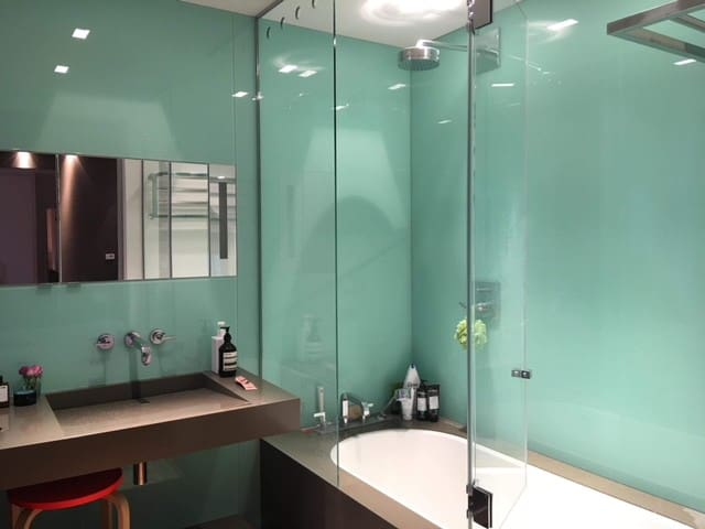 ensuite bathroom with tub and rainwater shower + luxurious glass walls.