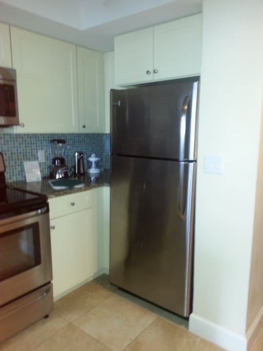 Kitchen has full size appliances including a range , microwave, cooktop, and microwave