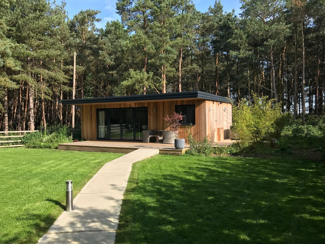 Lodge with private hot tub with woodland backdrop
