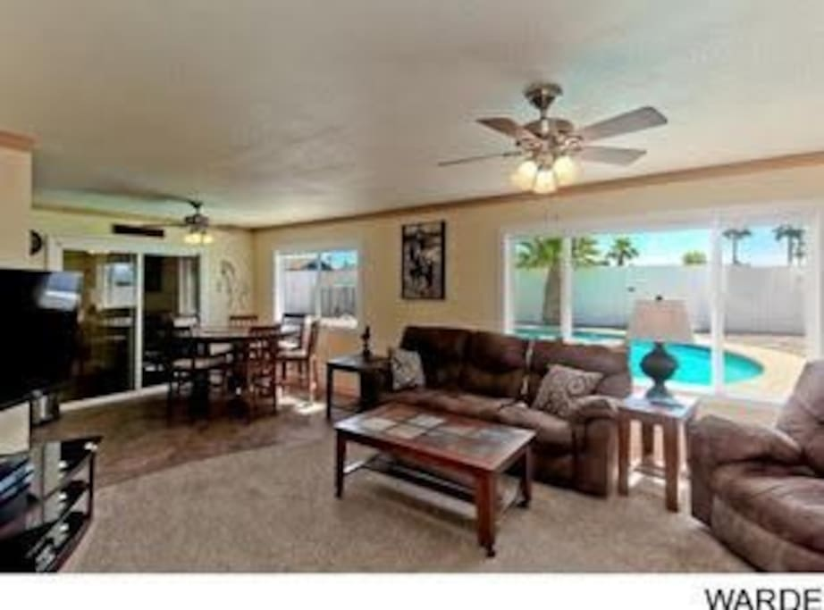 Living room and dinning area with excellent views of the backyard and pool.