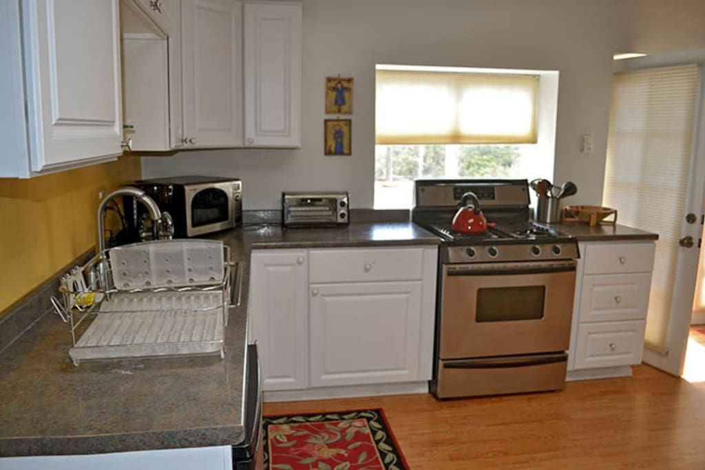 fully equipped kitchen with 4 burner gas stove and oven, small fridge, microwave, toaster oven, and automatic drip coffee maker