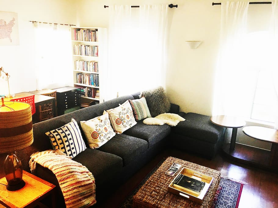 Large Living room includes: Flat screen TV, 4 Windows two large bay windows, small office.  Large chaise sofa and leather side chair.  Original art.