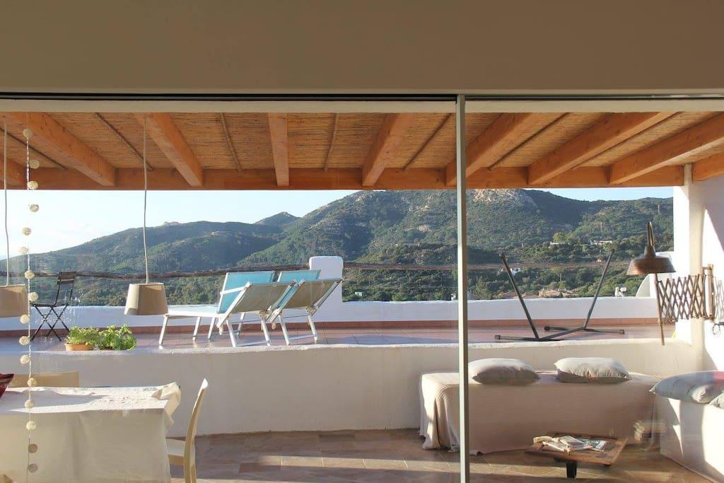 Ein grosser Teil des Jahres lassen sich die Fensterfronten in der Seitenwand versenken. Das Wohnzimmer bildet   mit der beschatteten Terrasse einen einzigen, grossen Wohnbereich.