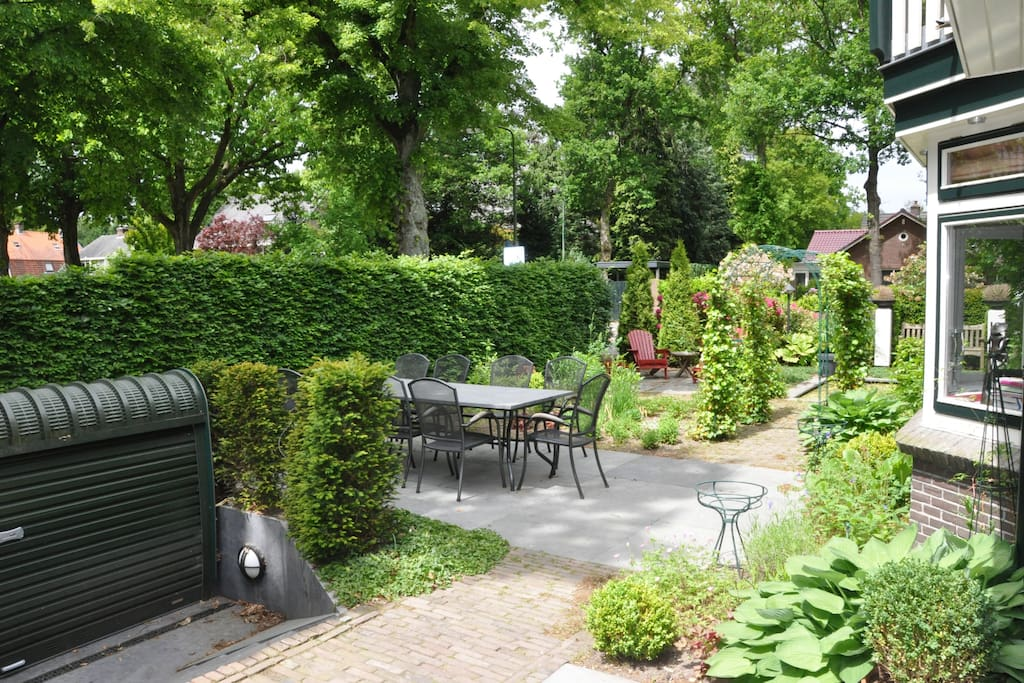 tuin met meerder zitjes en hardstenen tafel met 8 armstoelen
