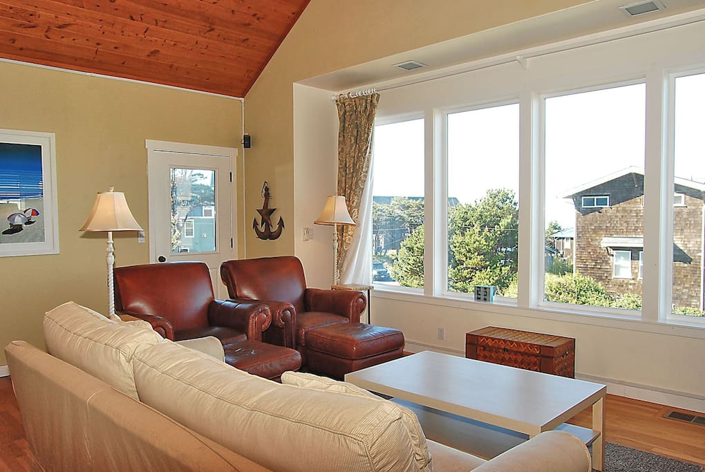 Seating in the living room in front of the large windows for natural lighting.
