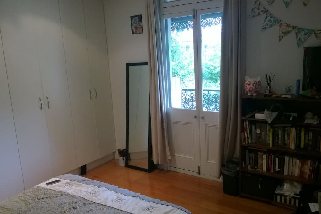 Wardrobe, full-length mirror and door to balcony.
