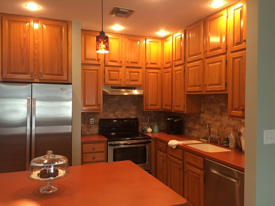 Stainless steel appliances include fridge/ freezer, oven, range, and dishwasher, nestled behind an eat-in island.