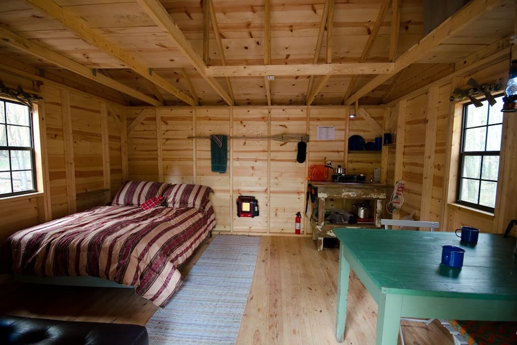 Hut interior.  Double bed, dinning table, kitchen area.  Also a couch which folds into another double bed.