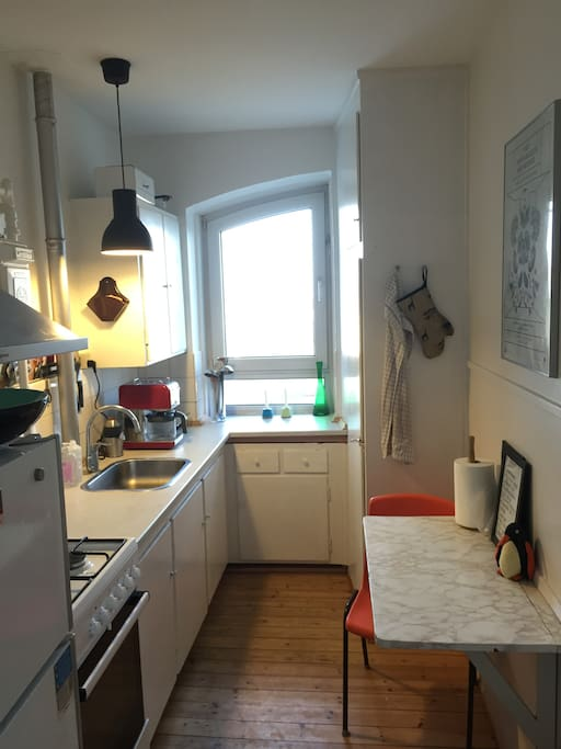 Kitchen with stove, refrigerator, coffee-machine and table for two.