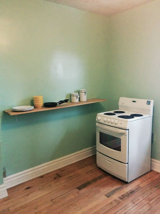 Kitchen supplies, electric stove, natural hardwood flooring.