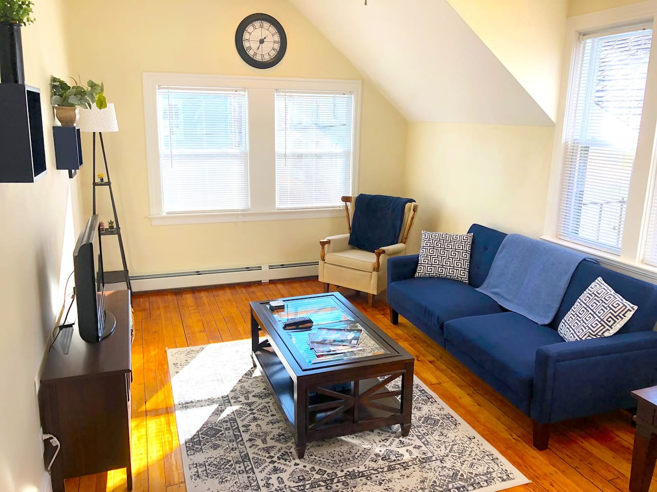 Living room is spacious and has 5 big windows that flood the apartment with natural light. It includes a large futon couch, comfy reading chair, solid wood coffee table, blankets, an HD TV, board games, Blueray player, and Netflix.