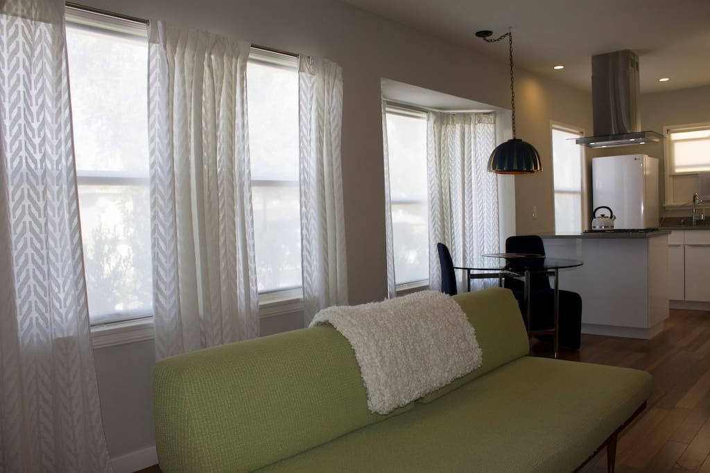 Sheer rollerblinds and curtains provide ample privacy while maintaining luminosity in the space. The common space of this bungalow is open and airy.
