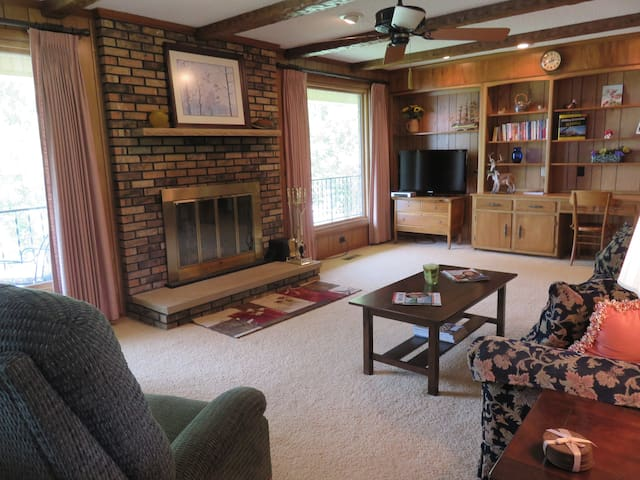 Spacious living room  with wood burning fireplace & large windows on lake side of home.