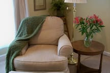 Cozy reading chair and ottoman in the larger bedroom.