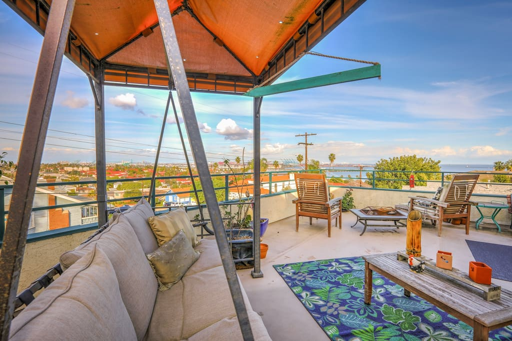 The 2BR unit boasts an expansive deck with city and ocean views, a barbecue grill, fire pit, ample seating, and a patio swing.