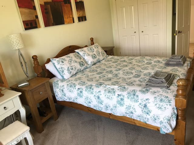 King size pine frame bed with large double wardrobe and bedside tables. This room also has an en-suite bathroom.