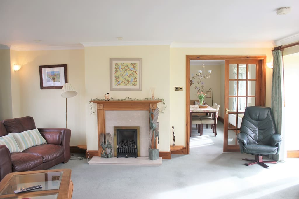 spacious lounge with french door leading to the garden and patio area
