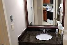 Hair dryer, sink and mirror outside of bathroom