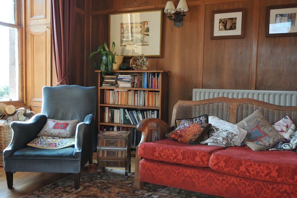 The Guest's Lounge, with comfy berger suites, lots of cushions and a log fire