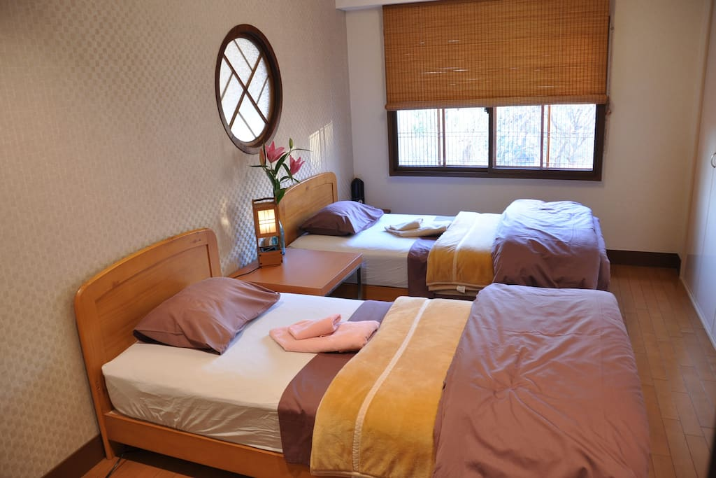 Main bedroom - double windows, comfi mattress, several pillows. Japonesque Western. Large cupboard/storage for suitcases.