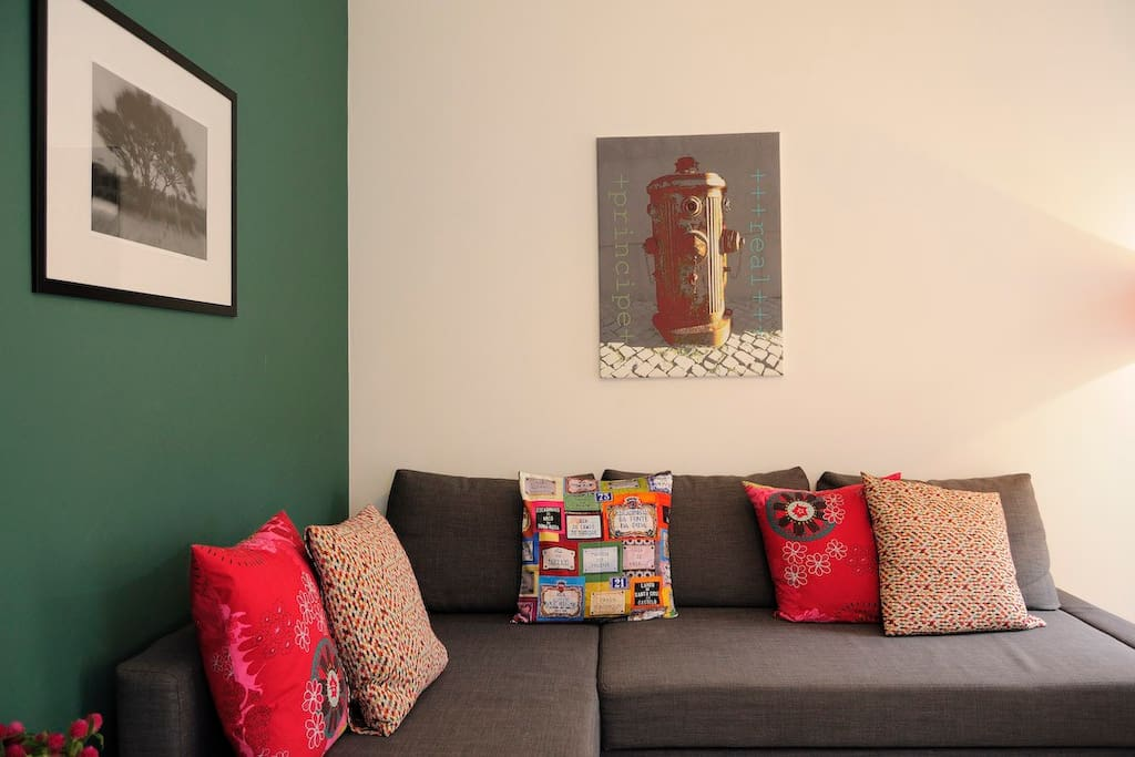 Sleeper couch with fire hydrant on wall, colourful handmade cushions