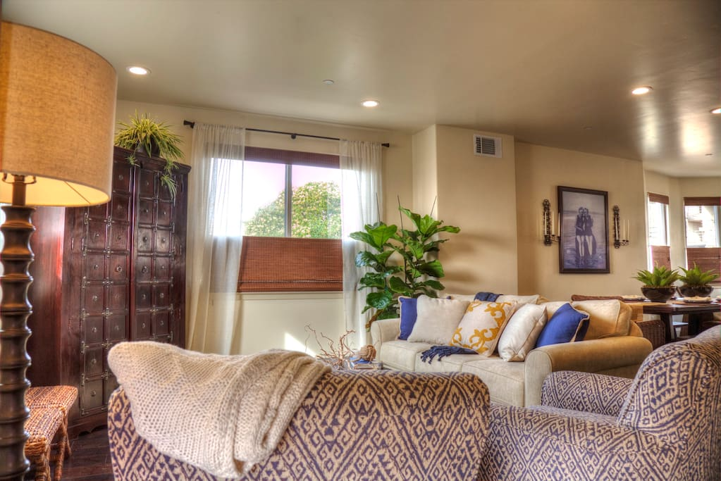Living Room has comfy couch, 2 swivel chairs, ottoman seating, large TV in cabinet. Several windows for natural light and cool ocean breezes.